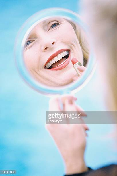 Woman looking at reflection in hand mirror, applying lipstick