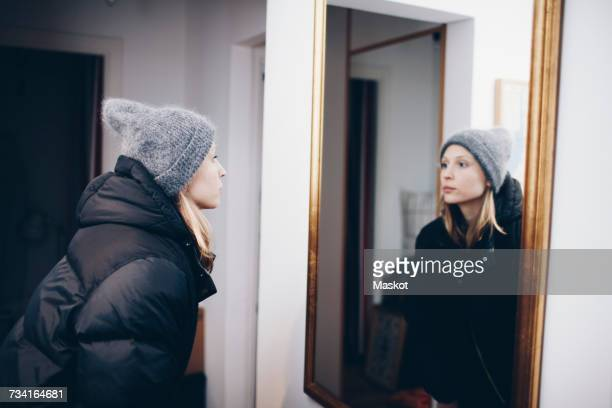 woman looking at reflection in mirror on wall - spiegel stockfoto's en -beelden