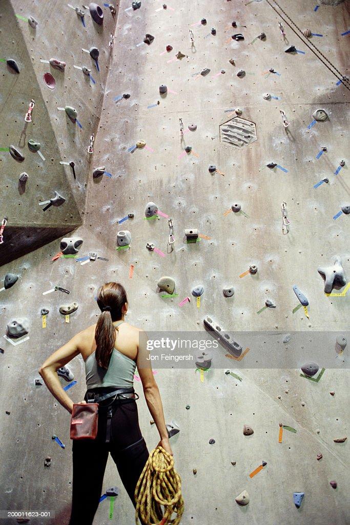 Woman looking at rock climbing wall : Stock Photo