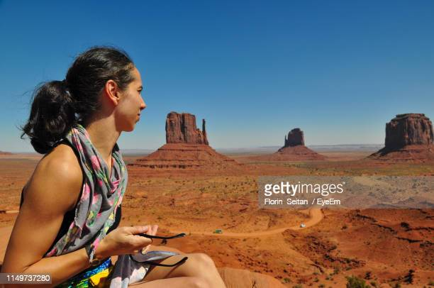 woman looking at rock formations against clear blue sky - florin seitan stock pictures, royalty-free photos & images