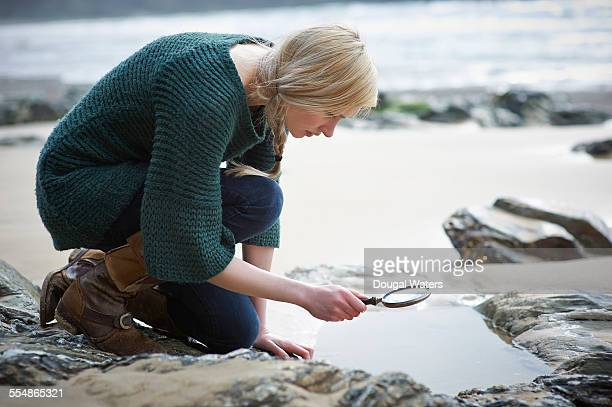 Woman looking at rocks through magnifying glass.