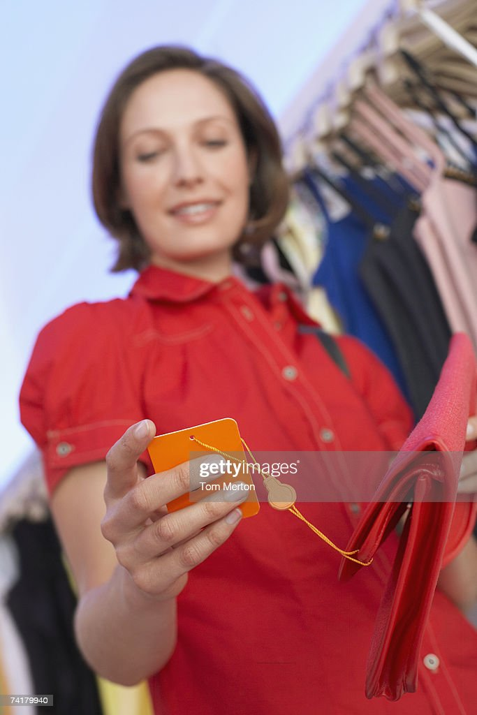 Woman looking at sales tag on purse : Stock Photo