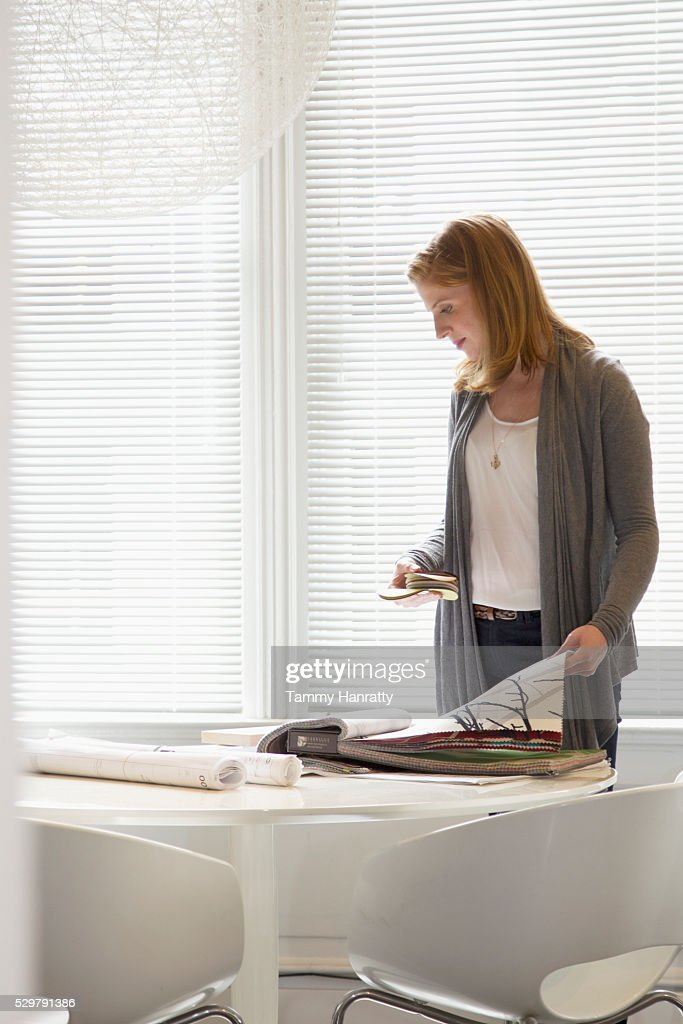 Woman looking at samples of wallpaper : Stockfoto