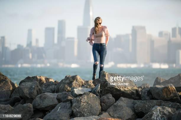 woman looking at san francisco skyline and bay bridge - treasure island california stock pictures, royalty-free photos & images