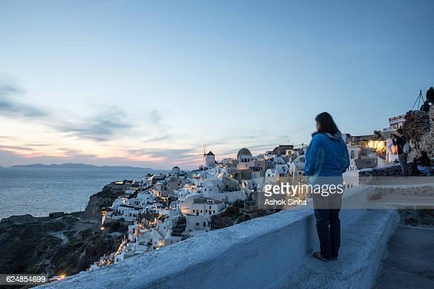 Woman looking at Santorini landscape at dusk