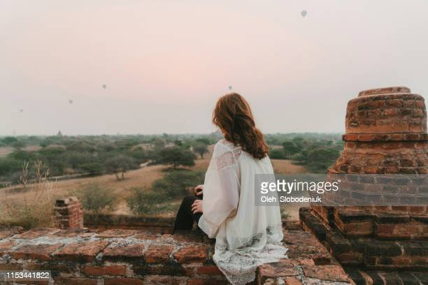 woman looking at scenic view of bagan heritage site from above - myanmar culture stock photos and pictures