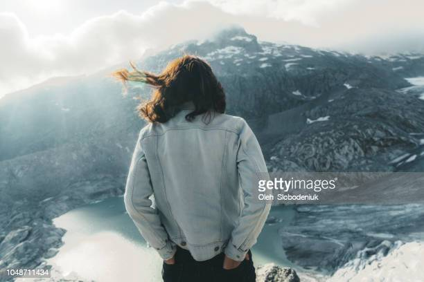 Woman looking at scenic view of glacier lake in Swiss Alps