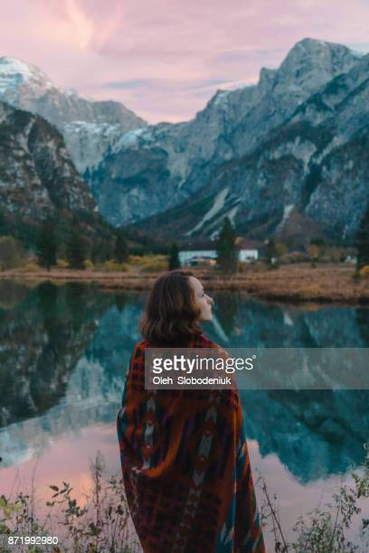 woman looking at scenic view of  lake in alps at sunset - maroon stock pictures, royalty-free photos & images