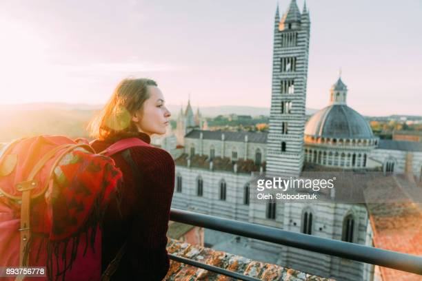 Woman looking at scenic view of Siena and Duomo di Siena from viewpoint