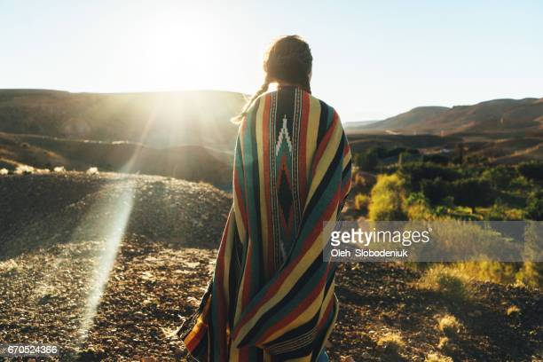 Woman looking at scenic view of valley in mountains