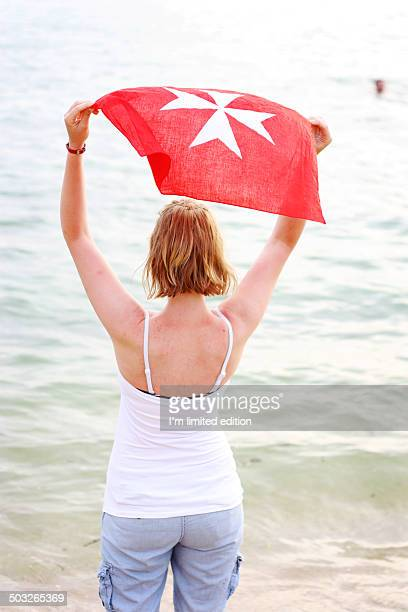 woman looking at sea holding a maltese cross scarf - maltese cross stock photos and pictures