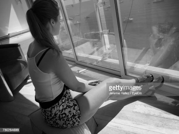 woman looking at sea through window while sitting in room - bandol photos et images de collection