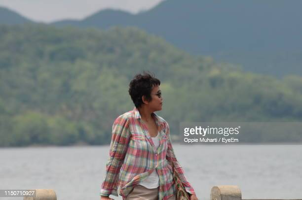 woman looking at sea while standing against mountain - oppie muharti stock pictures, royalty-free photos & images