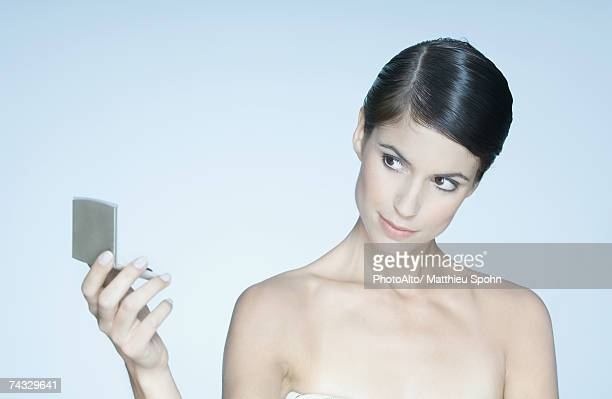 Woman looking at self in make-up mirror