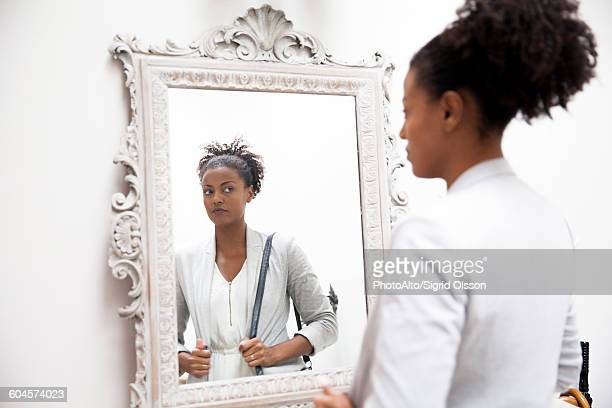 woman looking at self in mirror - woman in mirror stock photos and pictures