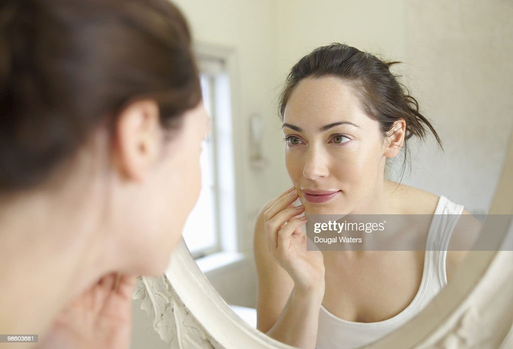 Woman looking at self in mirror. : Stock Photo