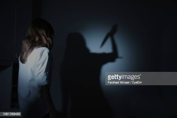 woman looking at shadow with knife standing on wall - mord stock-fotos und bilder