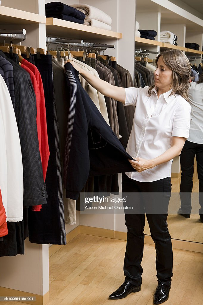 Woman looking at shirt in clothing store : Foto stock