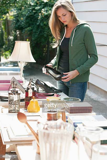woman looking at shoe at garage sale - garage sale stock pictures, royalty-free photos & images
