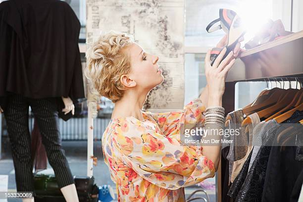 Woman looking at shoe in fashion designer shop.