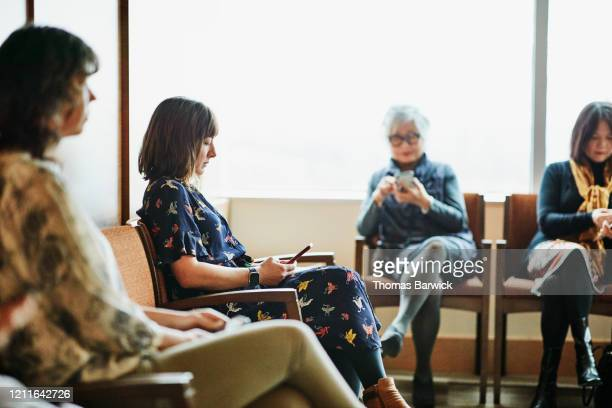 woman looking at smart phone while sitting in medical office waiting room - healthcare stock pictures, royalty-free photos & images