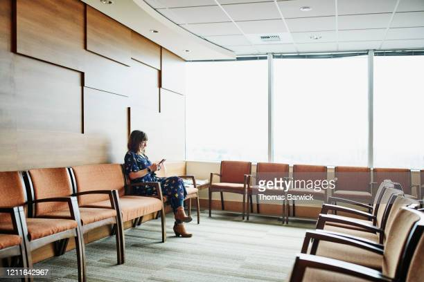 woman looking at smart phone while sitting in medical office waiting room - waiting room stock pictures, royalty-free photos & images