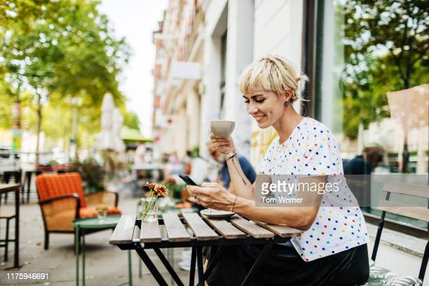 woman looking at smartphone while drinking coffee - lebensstil stock-fotos und bilder