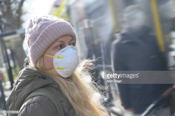 woman looking at something in a tram station. she is wearing a protection mask. unrecognizable close to her.  germany - 1918 flu pandemic stock pictures, royalty-free photos & images