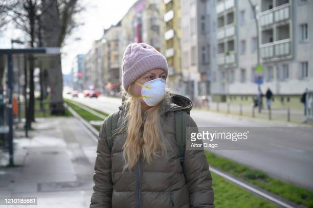 woman looking at something near the train tracks. she is wearing a protection mask. berlin, germany. - coronavirus stock-fotos und bilder