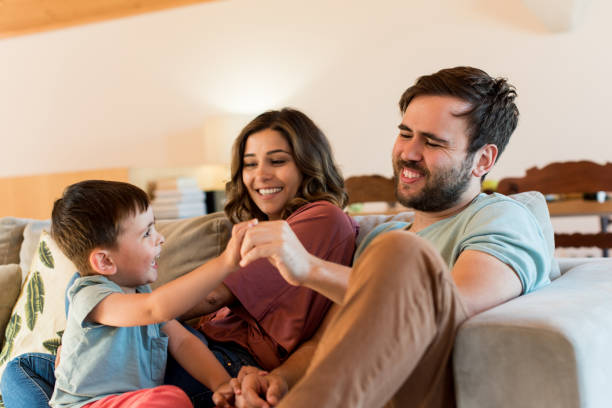 Woman Looking At Son Playing With Father While Sitting On Sofa