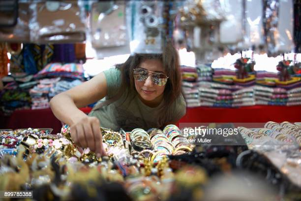 woman looking at souvenirs on market stall, bangkok, krung thep, thailand, asia - souvenir stock pictures, royalty-free photos & images