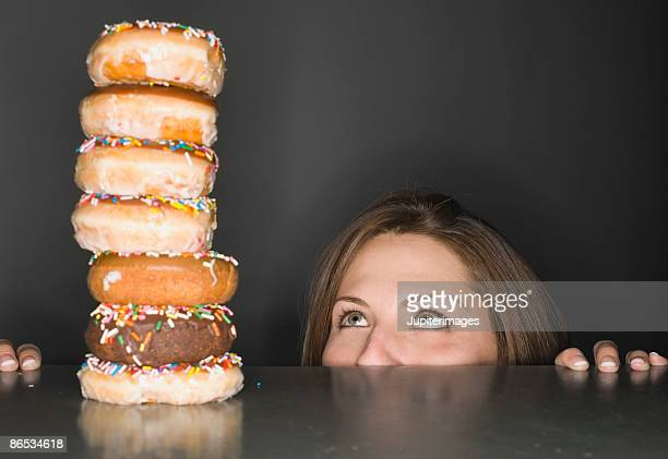 woman looking at stack of donuts in awe - abbuffata foto e immagini stock