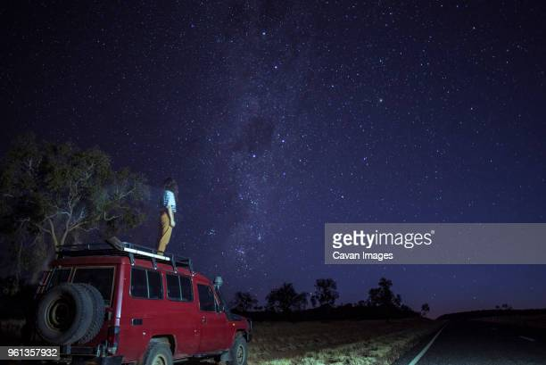 woman looking at star field while standing on car roof at desert - northern territory australia stock photos and pictures
