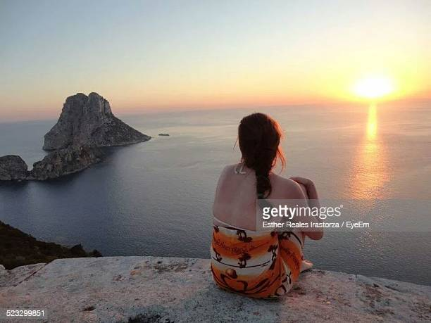 Woman Looking At Sunset Over Sea