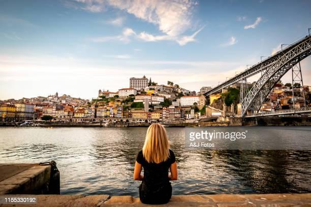 ポルトのドウロ川の夕日を眺める女性。 - ポルトガル ポルト ストックフォトと画像