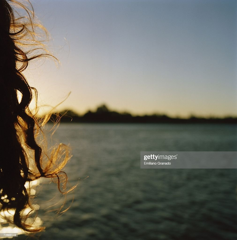 Woman looking at sunset over water : Photo