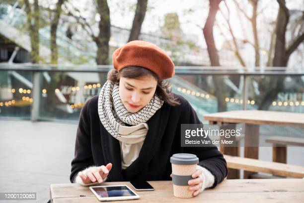woman looking at ipad, sitting in outdoor cafe. - on the move stock pictures, royalty-free photos & images