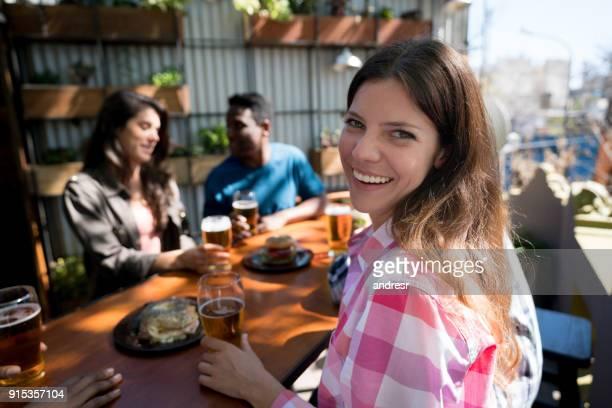 Femme regardant la caméra en souriant alors que ses amis profitent de bières et l'alimentation