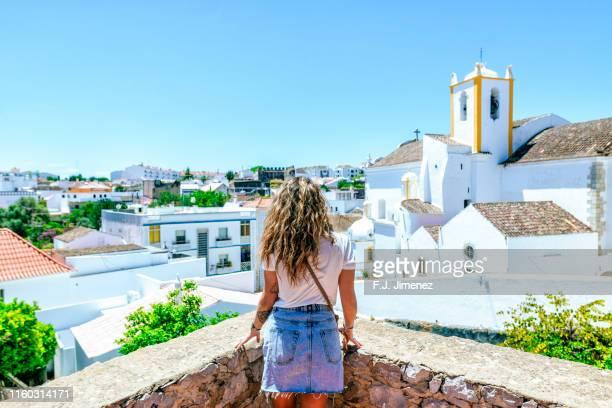 woman looking at the church of santa maria do castelo of tavira - tavira imagens e fotografias de stock