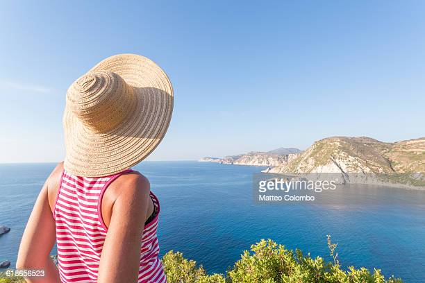 Woman looking at the coastline. Greece