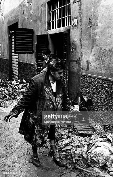 Woman looking at the damages caused to her house by the flood of the Arno River Florence November 1966