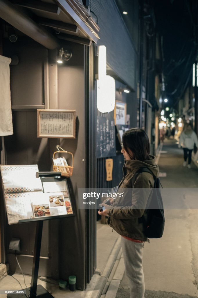 A woman looking at the food menu on the street, Kyoto, Japan : Stock Photo