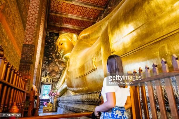 woman looking at the golden buddha, wat pho, bangkok - wat pho stock pictures, royalty-free photos & images