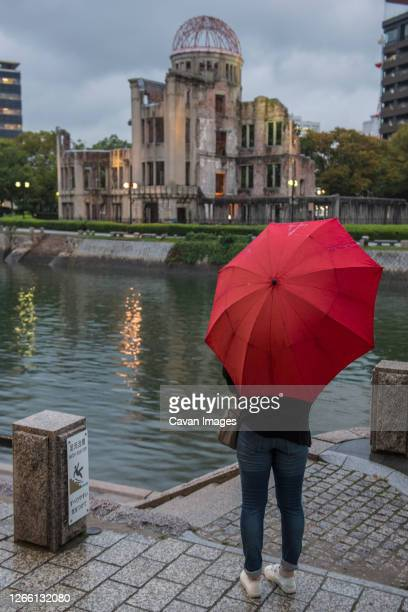 woman looking at the hiroshima, a-bomb (genbaku) dome in japan - atomic bombing of hiroshima stock pictures, royalty-free photos & images