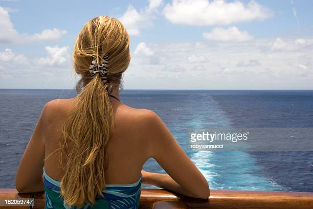 Frau blickt auf den Horizont von einem Schiff-deck