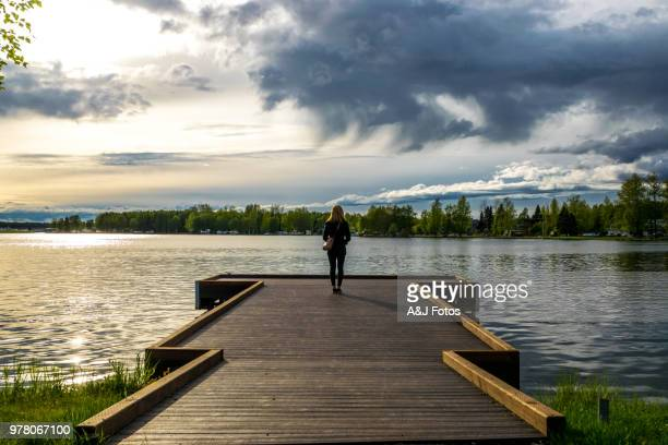 woman looking at the lake - anchorage alaska stock photos and pictures