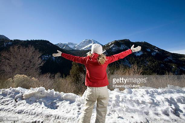 a woman looking at the mountains with her arms outstretched - red pants stock pictures, royalty-free photos & images