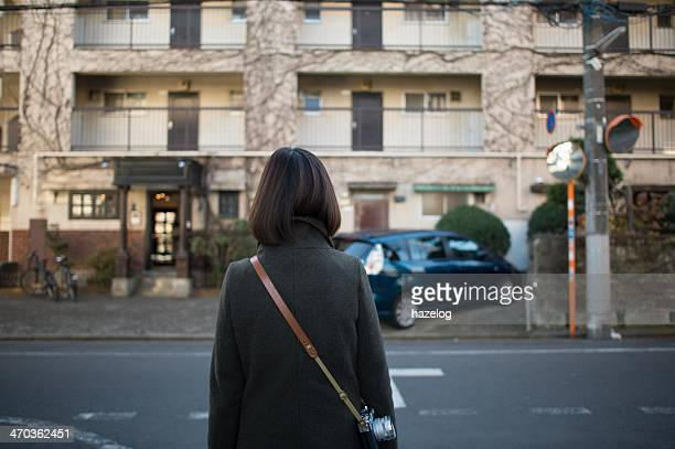 Woman looking at the old apartment building