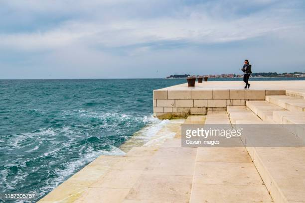 woman looking at the sea organ in zadar / croatia - croatia stock pictures, royalty-free photos & images