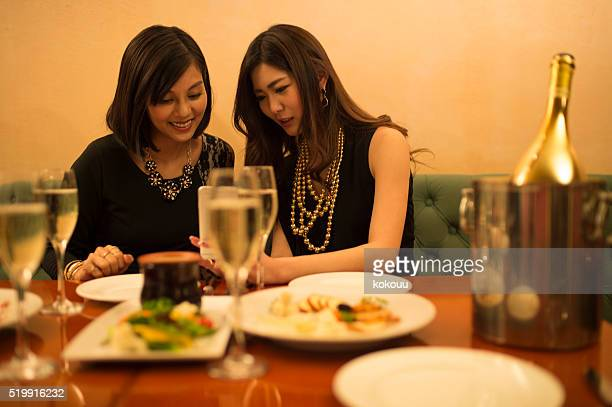 Woman looking at the smartphone while enjoying dinner